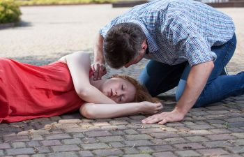 Unconscious woman lying on a pavement and a man checking her pulse