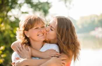 young woman cuddling and kissing her mother on the cheek
